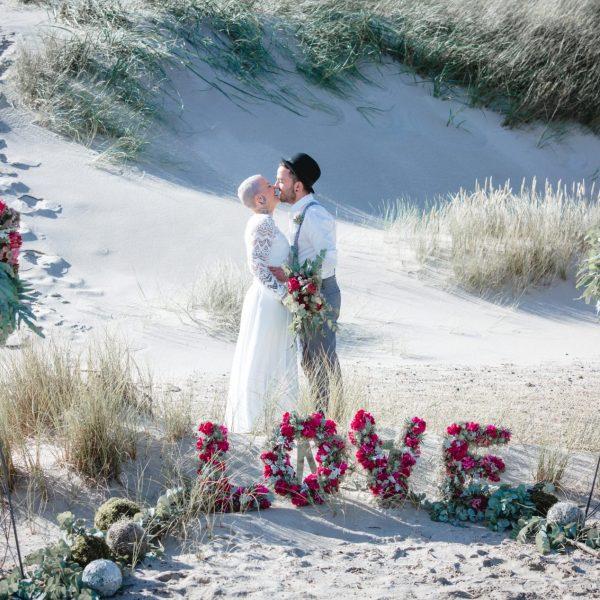 Hochzeit Strand Deko Buchstaben Brautpaar Brautstrauß Meer Blumen Steckschaum