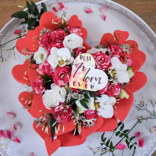 Muttertag Der Blütenwald rosarot geschmücktes Herz von Oben auf weißem Tisch aus der Vogelperspektive Closeup