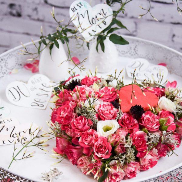 Muttertag Der Blütenwald rosa geschmücktes Herz auf Weißem Tisch Closeup